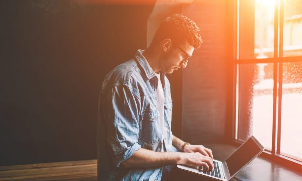 Caucasian male freelancer sitting near cafeteria window and typing new article in modern laptop application, young man blogger browsing wireless internet and updating profile in social networks